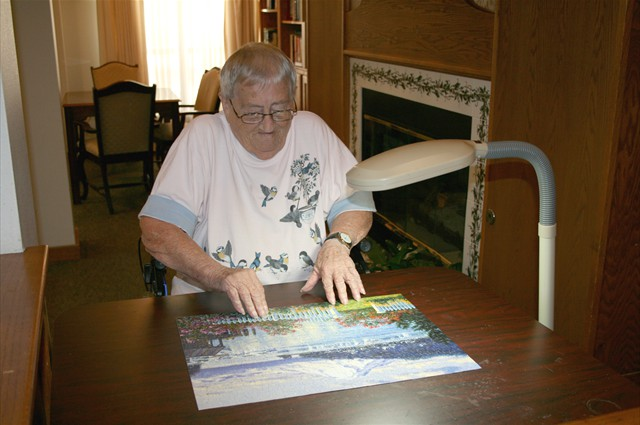 Resident putting together a puzzle in a common area